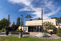 Two people in formal attire walk up to the main entrance of the lovely municipal auditorium at South Gate Park, showing the flag, lighting, mature trees, and streaks of clouds in a blue sky.
