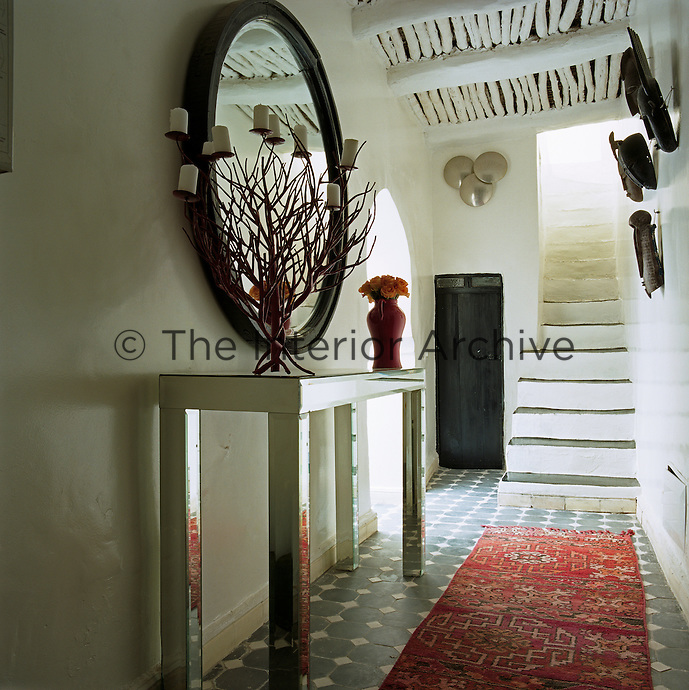 The entrance hall to the riad has a contemporary mirrored console table and candelabra and a traditional Moroccan rug on the tiled floor