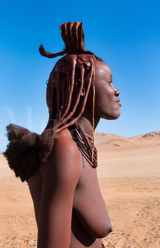 Namibia Africa remote nomadic Himba tribe young woman portrait in desert with traditional dress in desert of Hartmann Berge in Namib Desert topless breasts of black girl
