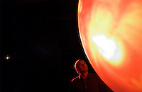 Bill Mutagh, a space weather forecaster at the Space Environment Center of the National Oceanic & Atmospheric Administration, or NOAA, examines a 6-foot  spherical projection screen displaying an image of the surface of the sun at NOAA in Boulder, Colo. The center predicts sun spot activity and solar storms. (Kevin Moloney for the New York Times)
