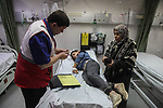 A Paramedical treats a wounded Palestinian protester, who was injured by Israeli security forces at the Gaza-Israel maritime border, at a hospital in Jabalia in the northern Gaza Strip, February 19, 2019. At least 20 Palestinians were injured as Israeli forces suppressed the 24th naval march along the northern besieged Gaza Strip, on Tuesday afternoon. Photo by Ramez Haboub