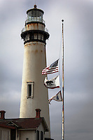 The United States,  California State  and  Lighthouse Service flags fly at half mast, or half staff, at Pigeon Point Lighthouse on the California coast near San Francisco.