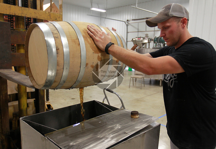 Adam Stumpf with empties a wooden barrel of bourbon.