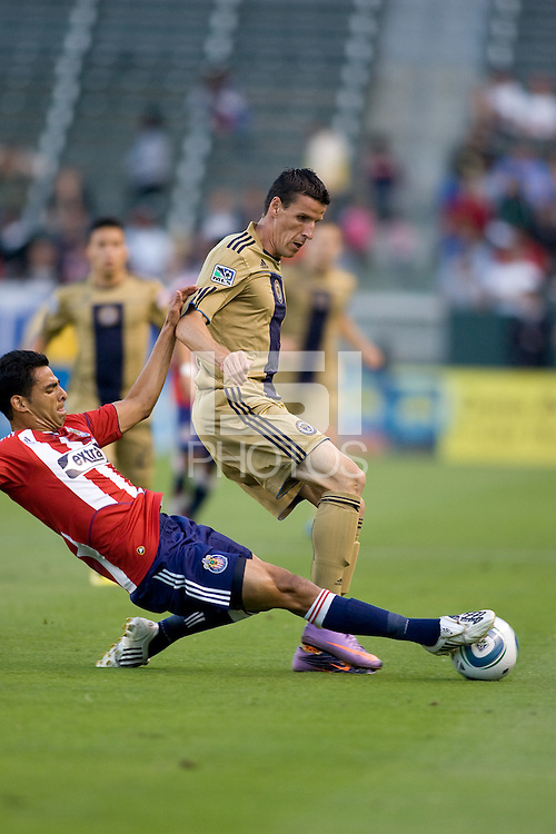 CD Chivas USA defender Michael Umana (4) tackles from behind on Philadelphia Union forward Sebastien Le Toux (9). The Philadelphia Union and CD Chivas USA played to 1-1 draw at Home Depot Center stadium in Carson, California on Saturday evening July 3, 2010..