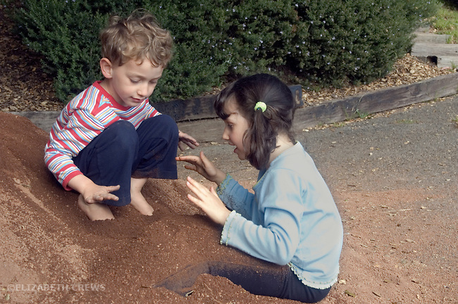 Berkeley CA  Siblings four and five burying themselves in a dirt pile at the park  MR