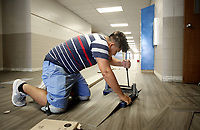 NWA Democrat-Gazette/DAVID GOTTSCHALK  German Figueroa, with Davis Flooring, cuts a piece of LVT tile Friday, July 6, 2018, in the hallway at Woodland Junior High in Fayetteville. New tile is being put down new tile in the hallways and cafeteria of the school. Northwest Arkansas school districts are busy working on facility improvement projects while staff and students are away for the summer break.
