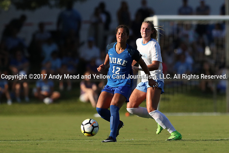 CARY, NC - AUGUST 18: Duke's Kayla McCoy (12) and North Carolina's Taylor Otto (behind). The University of North Carolina Tar Heels hosted the Duke University Blue Devils on August 18, 2017, at Koka Booth Stadium in Cary, NC in a Division I college soccer game.