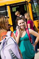 Series with multi-ethnic group of teenage students boarding and on a school bus. Using a smart phone and texting.
