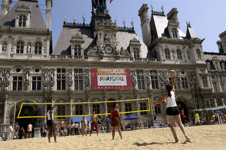 7/24/2004--Paris, France..A giant banner hangs from Paris' 'Hotel de Ville' promoting the city's 2012 Olympic bid with the saying 'L'Amour des Jeux', or 'Love of the Games'. In the foreground is 'Paris Plage', the annual 'beach' built by the city to entertain Parisians, featuring swimming pools and beach volleyball courts...Photograph by Stuart Isett.©2004 Stuart Isett. All rights reserved