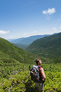 A hiker enjoys the view of the Great Gulf Wilderness from along the Sphinx Trail in the White Mountains, New Hampshire during the summer months.
