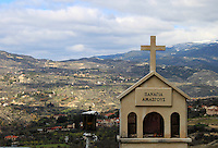 A cross on road towards Troodos mountains overlooking the hills of Troodos from a distance.