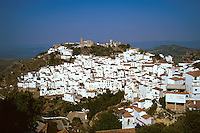 Whitewashed village in southern Spain built on a hillside with a church at the peak of the hill. Casares Andalucia Spain.
