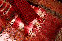A selection of paisley, tartan and checked blankets and shawls in varying tones of crimson and scarlet is laid out on a bed