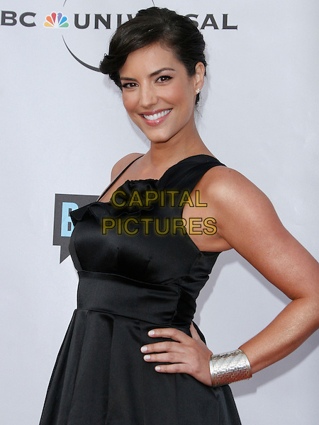GABY ESPINO . arriving at the The Cable Show 2010 To Feature An Evening With NBC Universal held at  Universal Studios Hollywood in Universal City, California, USA, .May 12th, 2010..half length black dress hands on hips smiling  silver cuff bracelet .CAP/ROT/AMB.©Adriana M. Barraza /Roth Stock/Capital Pictures