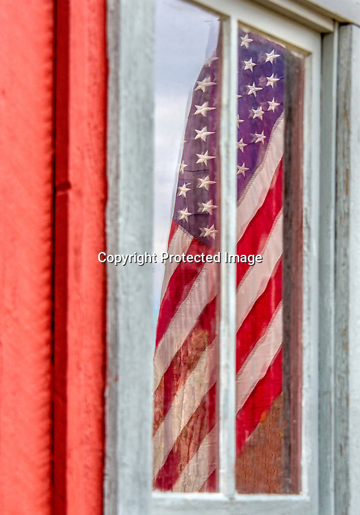 An American flag hangs in a window.