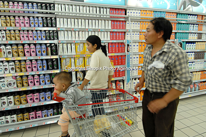 Customers pass racks of household shampoo products in a supermarket in Chengdu, China. A rapidly expanding middle class has created a large market for many products not previously sold in China..20 Sep 2006