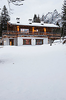 Exterior of chalet in the Italian Alps seen from the snow covered garden