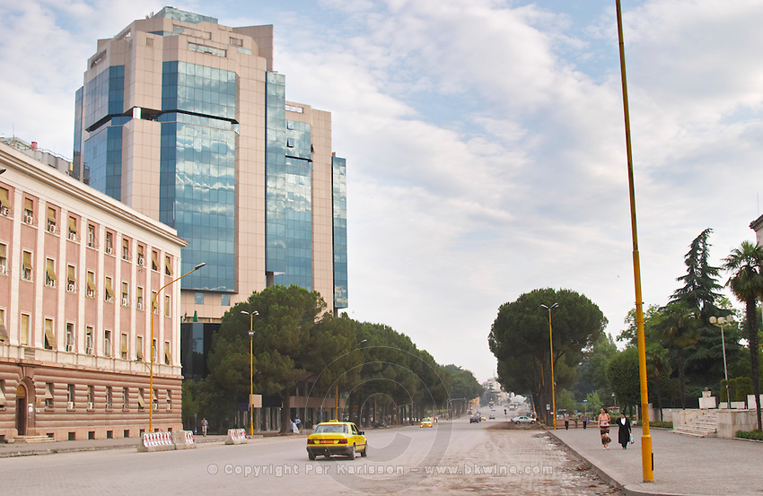 The modern Sky tower office complex On the boulevard Bulevardi Deshmoret e Kombit. Yellow Taxis on the wide street. Tirana capital. Albania, Balkan, Europe.