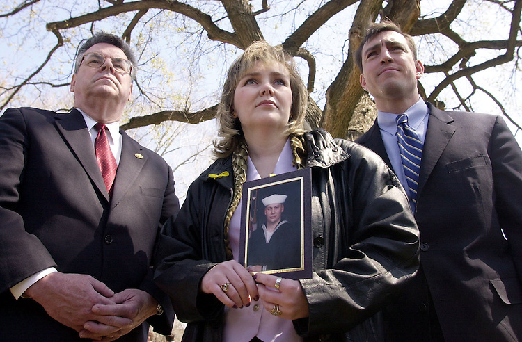 1airman040401 -- Reps. Peter King, R-NY, and Vito Fossella, R-NY stand beside Barbara DiStefano of Staten Island as she holds a picture of her brother Petty Officer Kenneth Richter who is one of the airmen being held in China.