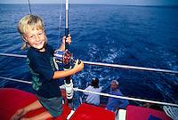 Young boy sports fishing on a family vacation, Kona, Hawaii