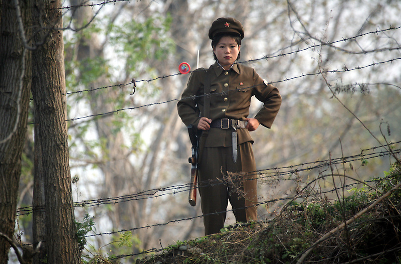 A female North Korean soldier stands guard along the bank of the Yalu River separating the DPRK from China.
