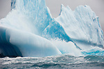 Waves crash against an iceberg in the South Atlantic Ocean.