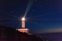 Punta Carena Lighthouse, on the famed Isle of Capri, Italy, shines in the darkness over the Gulf of Naples accompanied by the constellation Orion.