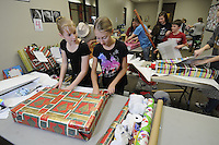 "NWA Media/ J.T. Wampler - Volunteers Anna Connolley, left, of Garfield, and Lindi Blevins of Lowell wrap gifts for seniors through ""Be a Santa to a Senior"" Home Instead Senior Care Monday Dec. 8, 2014 at the Frisco Mall in Rogers. The annual holiday tradition is in it's 11th year."