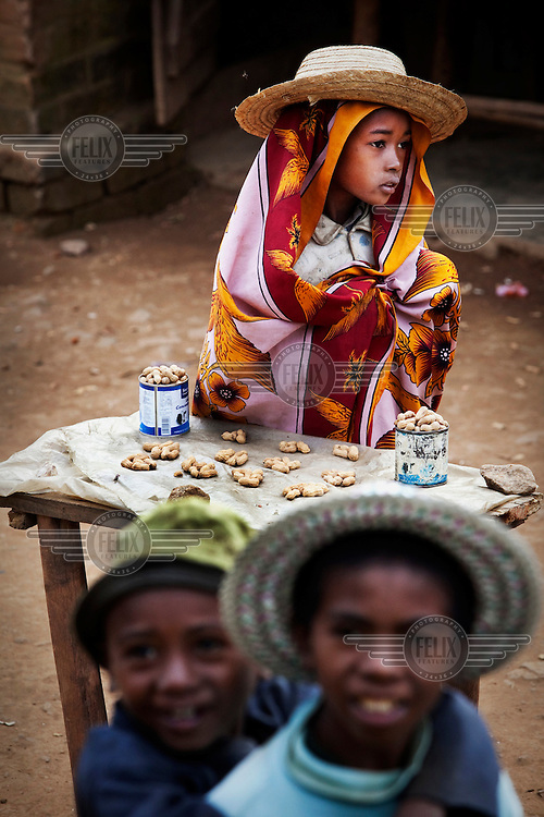 A girl sells peanuts, from a track side stall, to passengers on the train travelling between Fianarantsoa and Manakara.