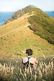 NEW ZEALAND, Coromandel Peninsula, Woman Sitting in Field of Grass, Ben M Thomas