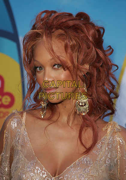 TYRA BANKS.The 2004 Teen Choice Awards held at The Universal Ampitheatre in Universal City, California .August 8, 2004.headshot, portrait, lace, plunging neckline, floral, dangling gold earrings, jewellery, cleavage.www.capitalpictures.com.sales@capitalpictures.com.Supplied By Capital Pictures