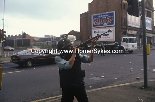 RUC Royal Ulster Constabulary police officer aims to shoot at a sniper Belfast Northern Ireland The Troubles 1980s.