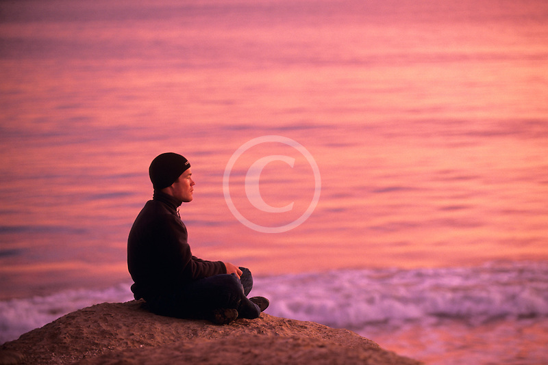 California, Santa Cruz, Man meditating at sunset
