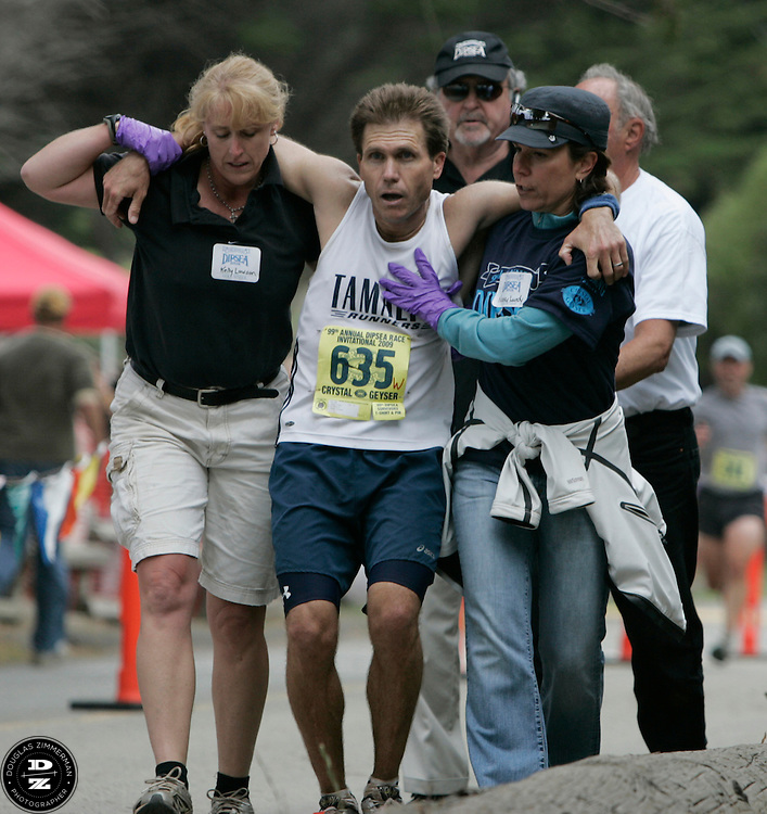 Bradley O'Brien (635) of Novato is helped my medical and race officials Kelly Lawson (left) and Nancy Lundy (right) to cross the finish line after stumbling, stalling, weaving and nearly falling over a few hundred feet from the finish line at the 99th running of the Dipsea Race at Sintson Beach State Park in Stinson Beach, Calif. on Sunday June 14th, 2009. O'Brien was one of several runners that needed assistance to cross the finish line during the race.