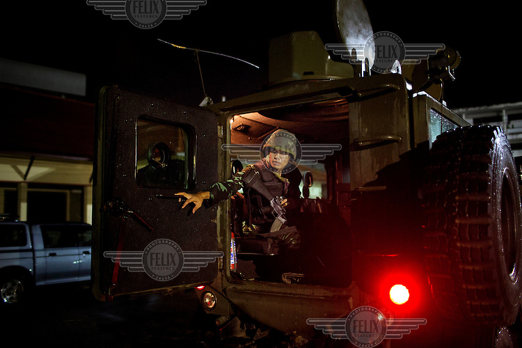 A soldier from the 23rd Pattani Battalion of the Thai Army closes the door of a Reva armoured troop carrier during a patrol in Pattani. /Felix Features