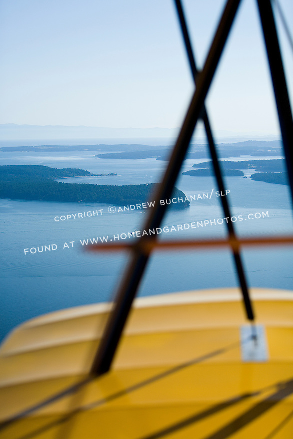 The deep blue green summer waters and muliple islands of Washington State's San Juan Islands as seen from the air through the wire cross braces of a classic biplane.
