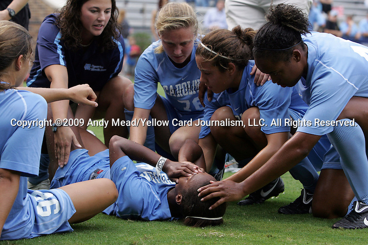 18 September 2009: North Carolina's Nikki Washington (center) is surrounded by a team trainer (dark blue shirt) and teammates Tobin Heath (98), Ali Hawkins (76), Casey Nogueira, and Jessica McDonald (right) after suffering an apparently serious injury to her right knee. The University of North Carolina Tar Heels defeated the Louisiana State University Tigers 1-0 at Koskinen Stadium in Durham, North Carolina in an NCAA Division I Women's college soccer game.