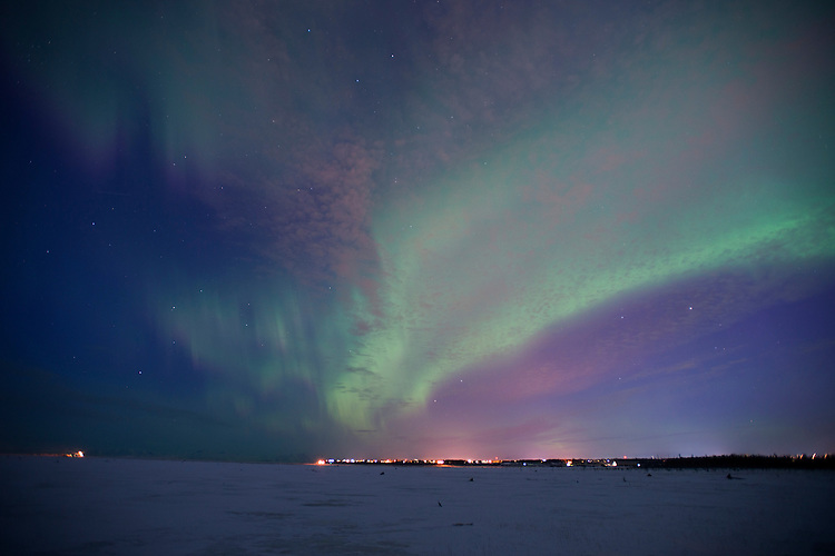 The aurora borealis fill the northern sky above the Kenai River flats and the city Kenai, Alaska. The bright green display of the northern lights at times filled the sky with green light.