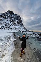 Young woman enjoying the winter landscape at Uttakleiv Beach, Vestavagoya Island, Lofoten Islands, Arctic, Northern Norway.