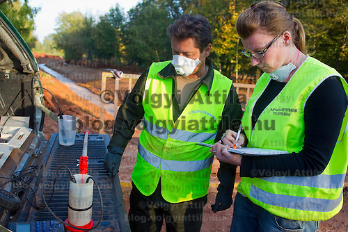 Officials from the green commando test the quality of the water in river Torna crossing Devecser in Hungary's Veszprem county that has been flooded by toxic sludge released by a dam accident in a nearby container. The toxic chemicals left its red marking on all the walls of the houses in and out and covered all moveable belongings and streets killing people and animals. Red sludge is a waste from bauxite fefining that has a strong caustic effect. The toxic flood covered an area of over 800-1,000 hectares (1,920-2,400 acres). Seven people were killed and more than 150 injured in the disaster. Pollution from the red sludge now spread into the local rivers killing all life in rivers Marcal and Torna and now it mixed into the main European waterway river Danube. Officials say there is no risk of a biological or enviromental catastrophe there.  Devecscer, Hungary, Saturday, 09. October 2010. ATTILA VOLGYI