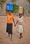 Two girls carry water in Lugi, a village in the Nuba Mountains of Sudan. The area is controlled by the Sudan People's Liberation Movement-North, and frequently attacked by the military of Sudan.