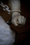 A close up of a statues clenched fist held with a chain