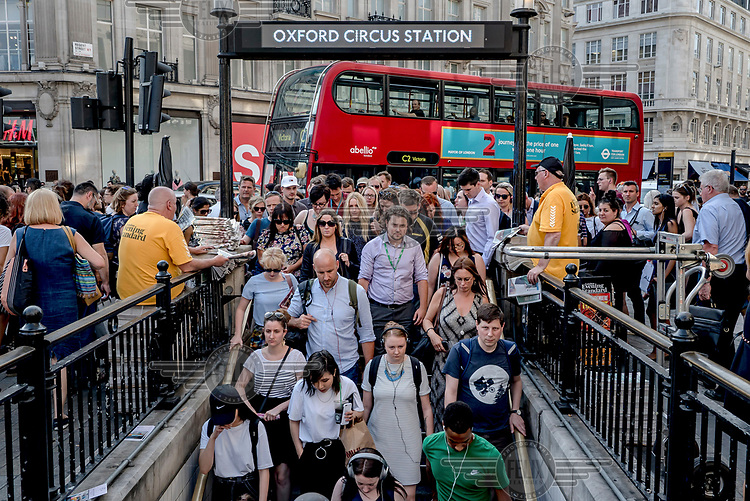 People make their way into Oxford Circus undergound station during rush hour.