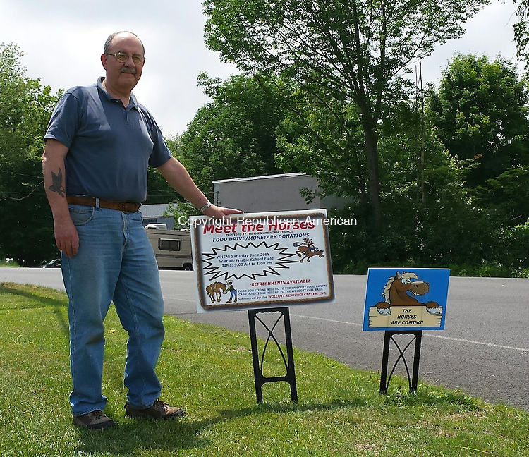 """WOLCOTT, CT - June 9, 2015 - 060915AL02 - Joe Discepolo, a volunteer with the Wolcott Resource Center, holds a sign advertising a 'Meet the Horses' food drive and fundraiser from 9 a.m. to 1 p.m. June 20 on the Frisbie School field. The organization, which runs the Wolcott Food Pantry, has placed signs that say """"The Horses are Coming"""" throughout town."""