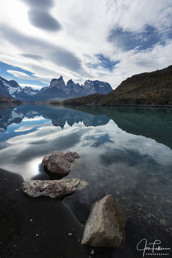 Wide-angle view of the Cuernos del Paine with rocks and Lake Pehoe in the foreground.  Torres del Paine National Park in Patagonia, Chile.  A UNESCO World Biosphere Reserve. The Cuernos and clouds are reflected on the lake surface.