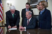 Director of National Intelligence Dan Coats (2-R), with his wife Marsha Coats (R) and family members, watch as United States Vice President Mike Pence (L) signs an affidavit during a swearing in ceremony in the US Capitol in Washington, DC, USA, 16 March 2017.<br /> Credit: Shawn Thew / Pool via CNP