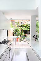 A modern white minimalist galley kitchen has a full height glass sliding door that leads to a decked terrace and the garden beyond.