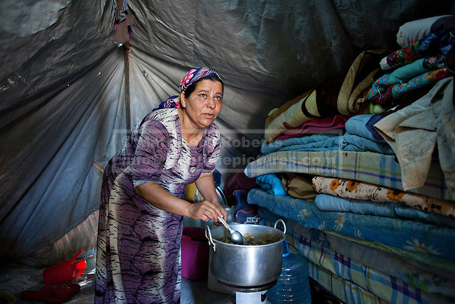 Hadia Oso Dawed (40), a Syrian refugee, prepares lunch for her family inside her tent at the Domiz Refugee Camp in Iraqi-Kurdistan. Originally from Hassaka province in Syria, Hadia crossed the border into Iraq in February 2013 when shelling in near her home became heavier and she and her husband could no longer provide food or safety for their 5 children. The camp, run by the UNHCR and International Rescue Committee, is home to around 4,500 refugees who have fled from the ongoing Syrian civil war with up to 400 new inhabitants arriving every day.  Built on the site of a former Iraqi Army base that was bombed during the 2003 Coalition forces invasion of Iraq, the camp was cleared of cluster bombs and unexploded ordnance by the Mines Advisory Group (MAG), a demining NGO working in Iraqi-Kurdistan.