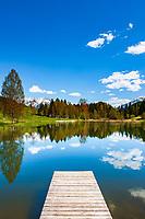 Oesterreich, Tirol, bei Fieberbrunn: der auf 859 m Hoehe gelegene Lauchsee ist ein Moorsee mit einer Badegelegenheit Moorbad Lauchsee, im Hintergrund die schneebedeckten Leonganger Steinberge (links) und die Kitzbueheler Alpen | Austria, Tyrol, near Fieberbrunn: moorlake Lauchsee with Leonganger Steinberge mountains (left) and Kitzbuehel Alps