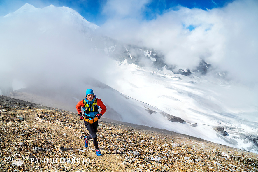 A trail runner heading for the Barrhorn (3610 meters), the highest peak in Switzerland that has a trail to the top. Turtmenntal, Switzerland. in the background is the Weisshorn and Bishorn in clearing clouds.